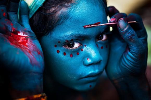 """Ganadora de Mérito. """"Maquillaje divino"""" por Mahesh Balasubramanian. Tomada durante el festival de Mayana Soora Thiruvizha, que tiene lugar cada mes de marzo en el pequeño pueblo de Kaveripattinam, el día después de Mahashivarathiri (la gran noche de Shiva). El festival está dedicado a Angalamman, una deidad guardiana feroz adorada ampliamente en el sur de la India"""