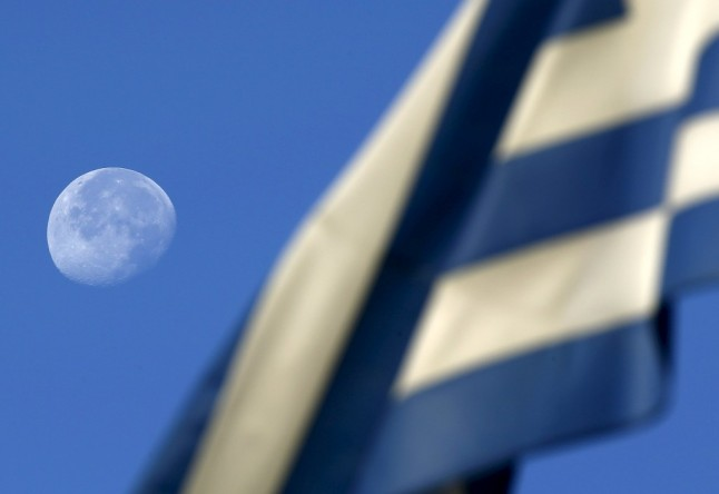 A lua brilha no horizonte junto a escola em Atenas onde os gregos votam hoje REUTERS/YANNIS BEHRAKIS