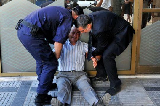 Giorgos Chatzifotiadis, 77 ans, est aidé par un employé de la banque et un policier alors qu'il pleure devant l'établissement, le 3 juillet 2015 à Thessalonique (Photo SAKIS MITROLIDIS. AFP)