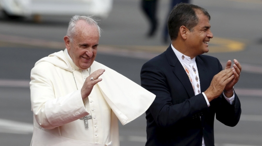 Pope Francis (L) blesses the audience as Ecuador's President Rafael Correa applauds after Pope Francis landed in Quito, Ecuador, July 5, 2015. Pope Francis landed in Ecuador's capital Quito on Sunday to begin an eight-day tour of South America that will also include visits to Bolivia and Paraguay. On his first visit as pontiff to Spanish-speaking Latin America, the Argentina-born pope is scheduled to conduct masses in both Quito and the coastal city of Guayaquil before flying to Bolivia on Wednesday. REUTERS/Jose Miguel Gomez